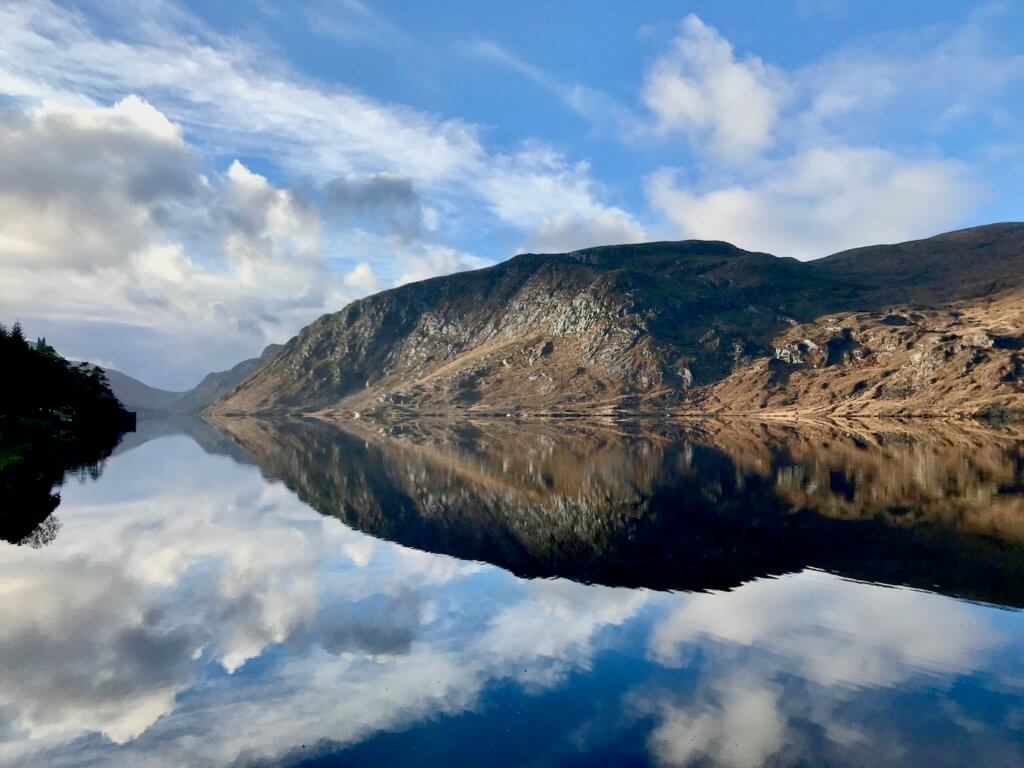 The beautiful Loch at Glenveagh National Park is a perfect mix of placid water, reflecting the massive hills of granite and tight green grass as well as the blue sky with puffy white clouds.