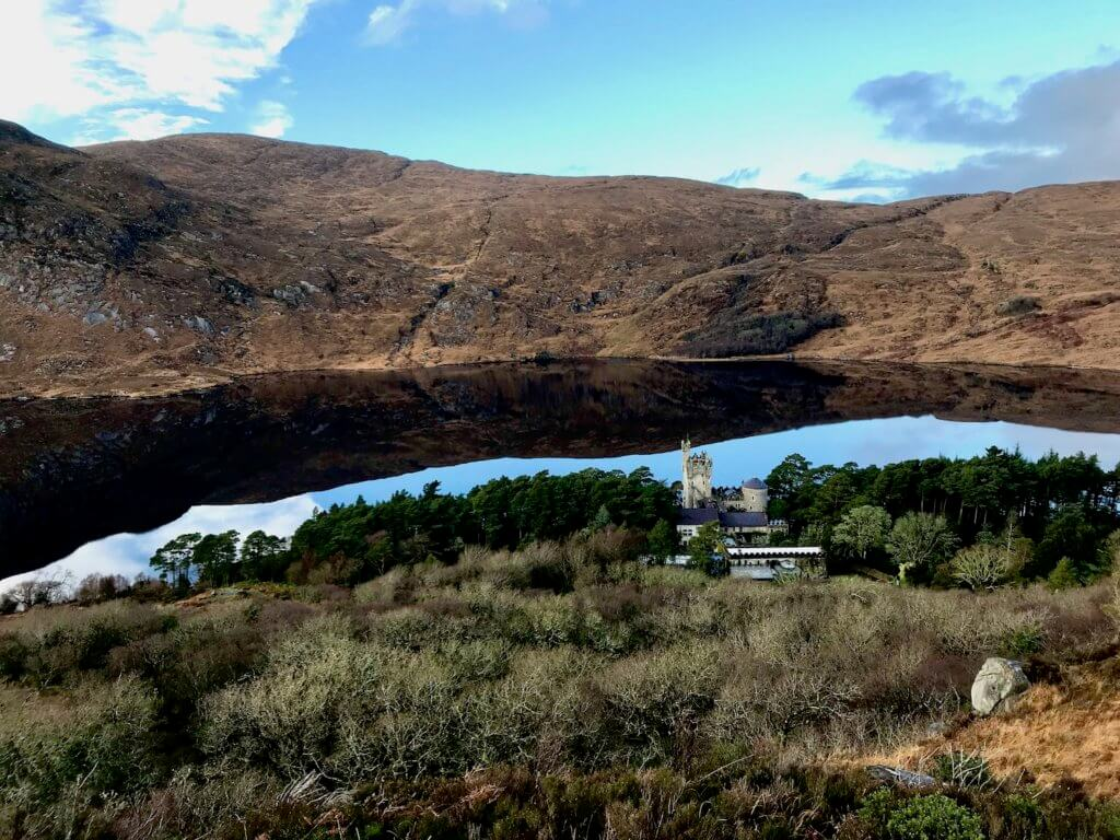This view of Glenveagh National Park in Donegal Ireland looks down at the 20th century castle which is almost hidden amongst a large grove of green trees following the bank of the vast lough, with still waters reflecting the blue sky and the tall hills on the opposite side.