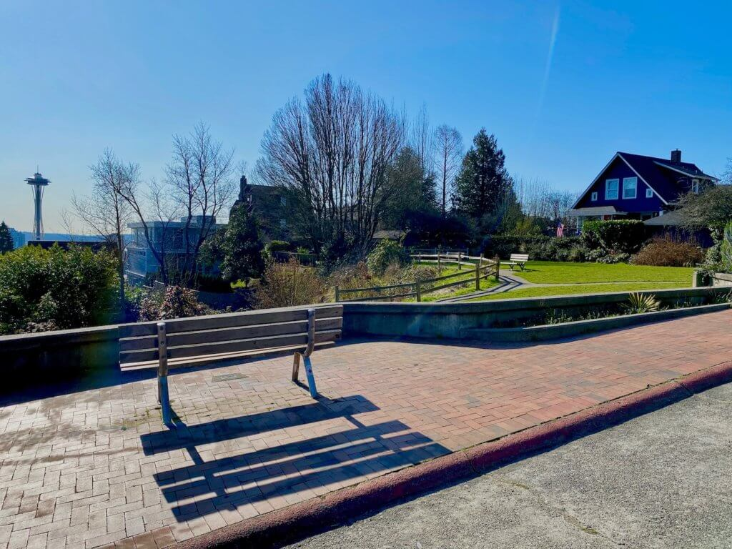 The views of Seattle from Bhy Kracke Park are evident in this shot by the scene with Space Needle in background surrounded by blue sky. The park bench and shadow cast on the red bricks is the the foreground just after a concrete roadway. There is an area of bright green grass with a family home in the background.