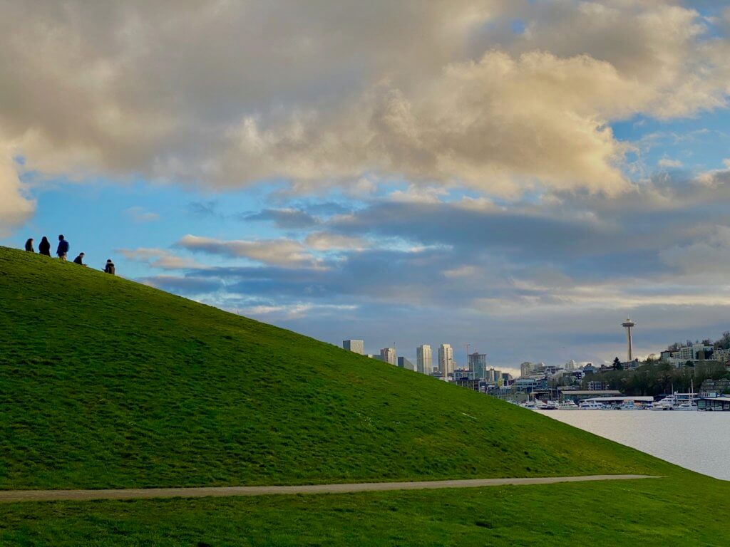 Gasworks Park is situated at the north end of Lake Union. This view of Seattle shows a diagonal slope of bright green grass with five people relaxing on the top of the hill looking toward the skyline of Seattle, including the Space Needle. A tiny triangle of grayish Lake Union pushes through the right side of the photo while dark clouds move amongst pops of powder blue sky.