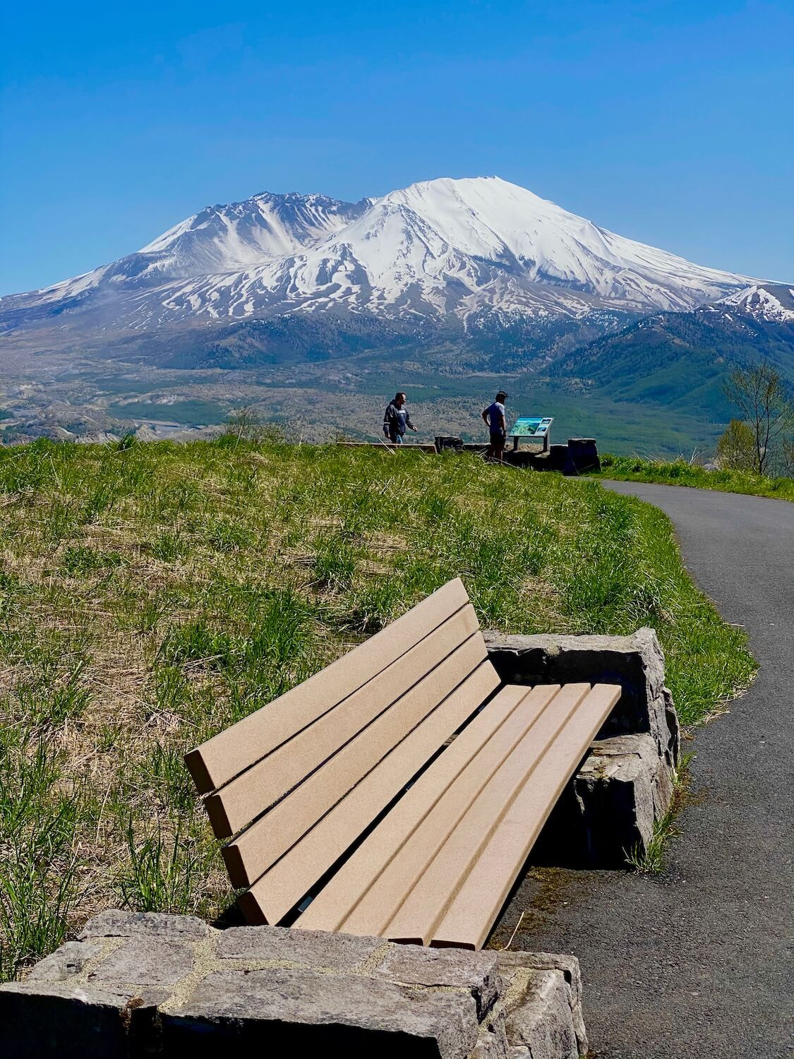 Mt. St. Helens from a viewpoint turnoff on Highway 504.  The green grass and brown seating bench in the foreground lead to two tourists reading a road marker on a paved trail.  The the majestic volcano crater of Mt. St. Helens rises up in the background.  The mountain is covered in white snow with veins of gray rock exposed.  The blue sky sets a vibrant background to this scene.