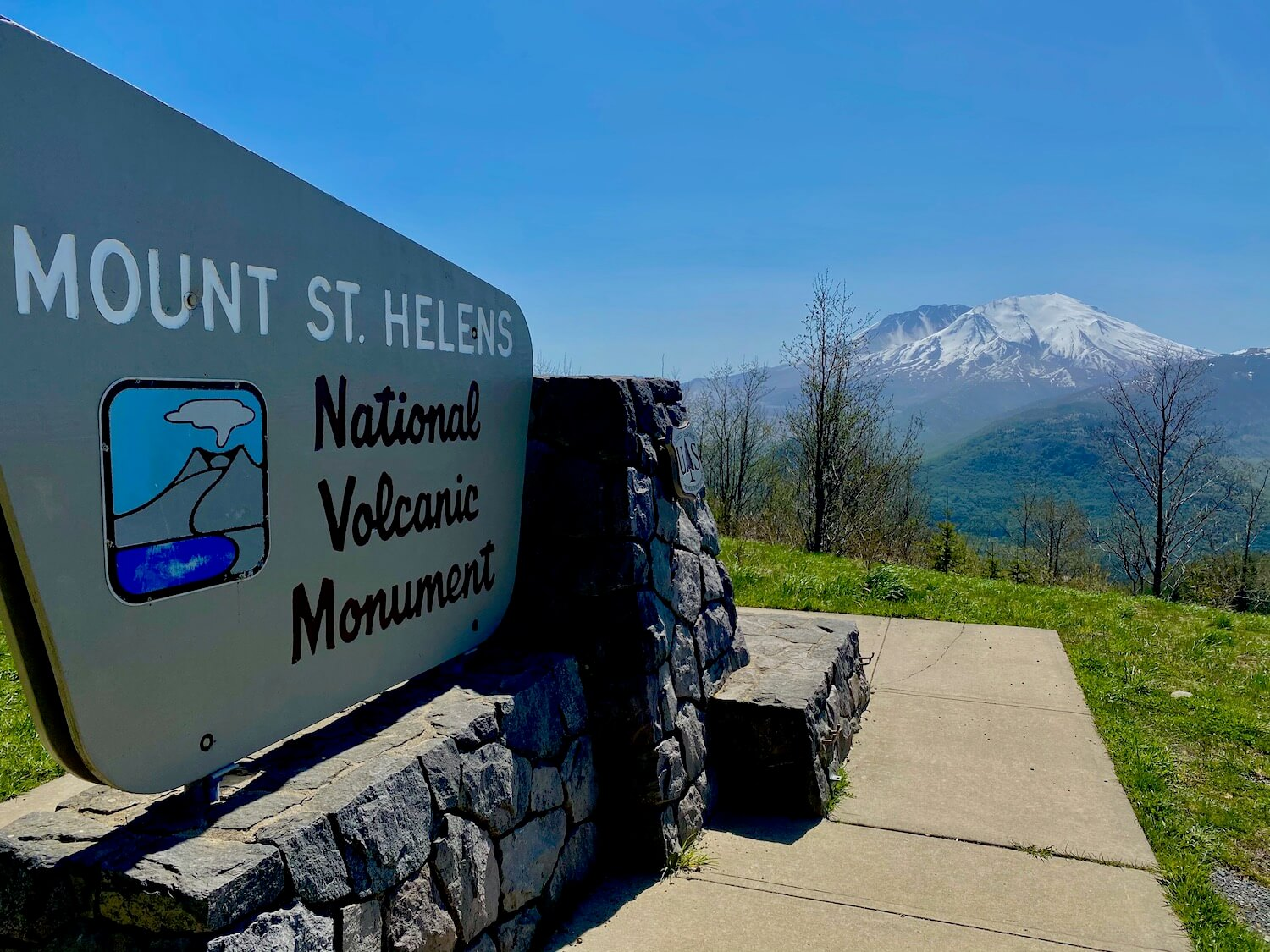 The entrance sign to the Mount St. Helens National Volcanic Monument. The sign is housed on a rock wall and sits on the side of a steep hill facing the snow covered volcano in the distance. The grass near the sign is bright green with the blue sky.