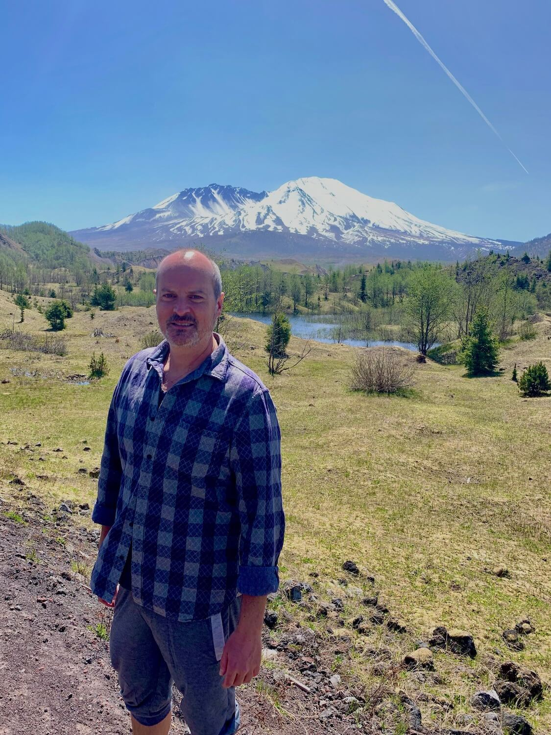 Selfie of Matthew Kessi n front of a mountain lake surrounded by Low green cover brush and alders.  Snow covered Mt. St. Helens rises up in the background with a blue sky.