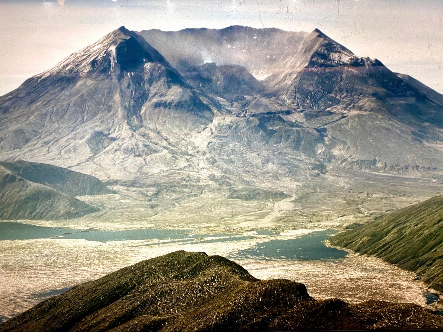 A photo from an exhibit at the Mt. St. Helens Visitor Center showing the aftermath of the massive landslide and steam explosion that occurred on May 18, 1980.  The smoldering crater is releasing steam around a charred black mountain that leads down a dusty landscape to Spirit Lake, now almost filled with floating logs of the trees destroyed in the blast.