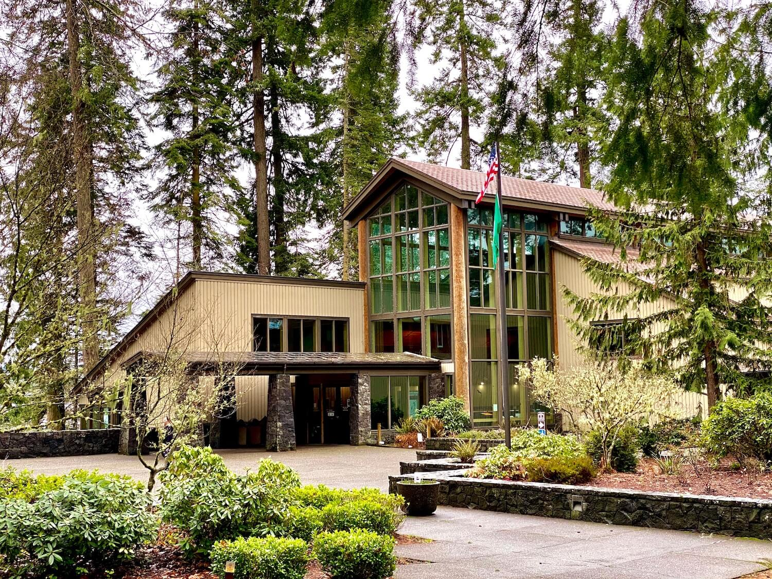 The exterior of Mt. St. Helens Visitor Center is a mixture of wide glass windows, stone pillars and wood siding, all in brown hues.  The building is surrounded by tall douglas fir trees.