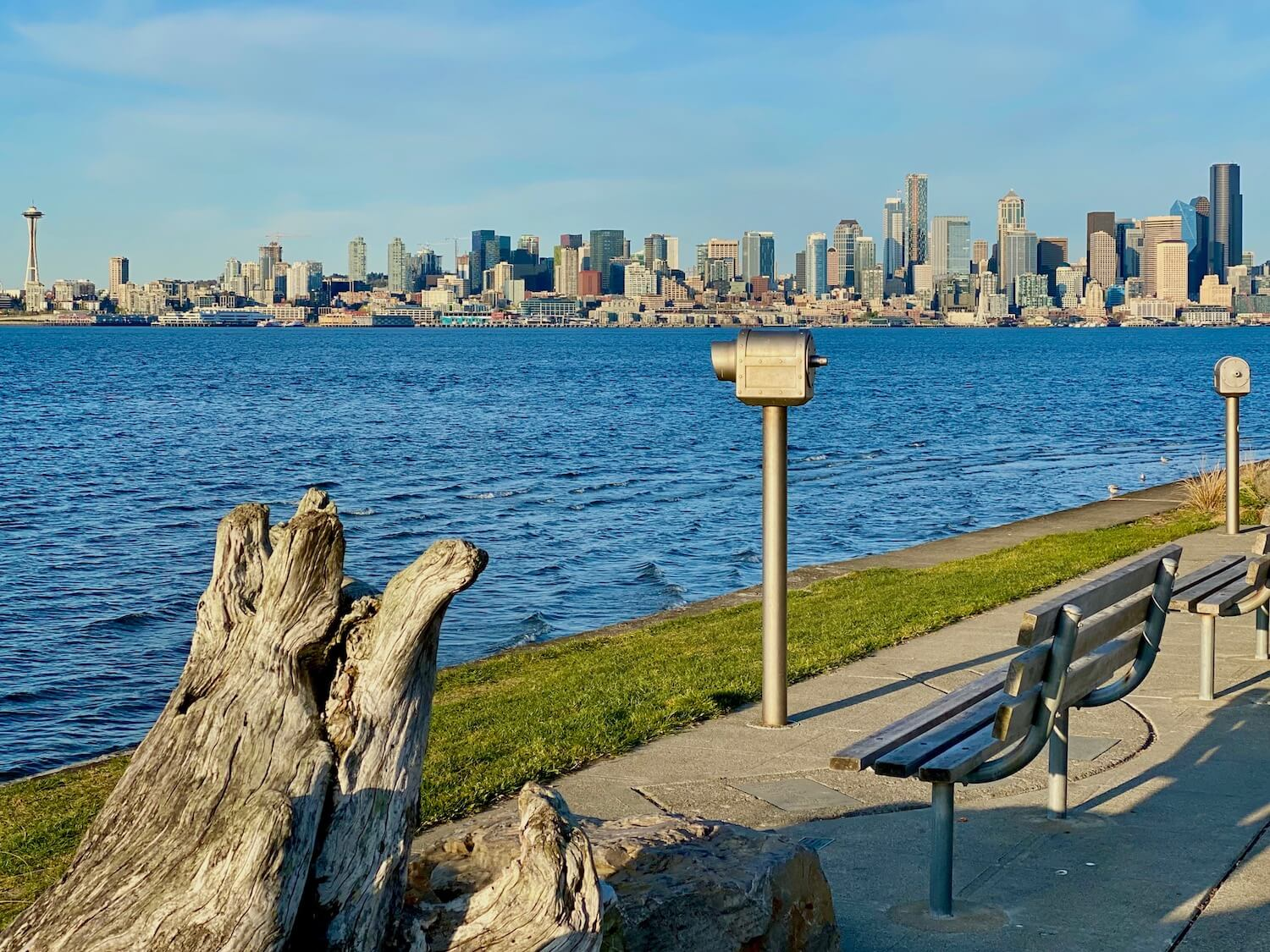 Alki Beach and West Seattle offer sweeping views of the city and this shot shows the skyline from the Space Needle to the tallest black building, Columbia Center. The city is across Eliot Bay, which is a rich blue color. In the foreground is a large piece of driftwood as well as two silver telescopes and two slatted benches.