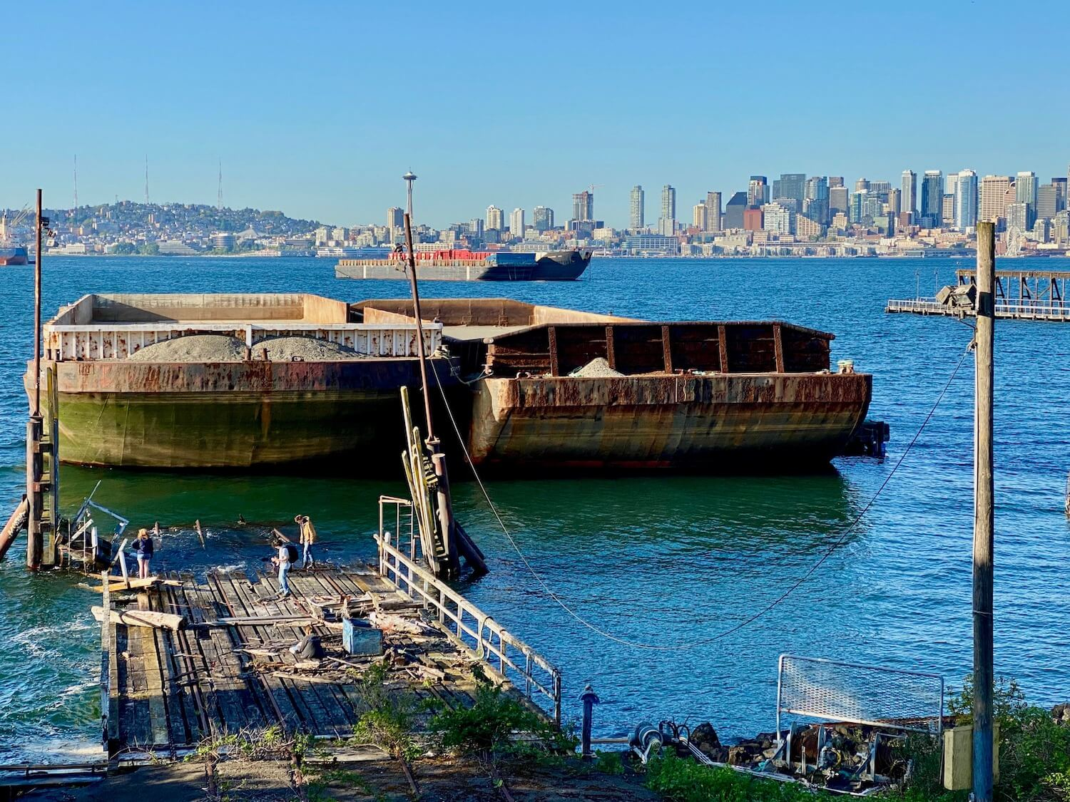 Crossing from Jack Block part to Joe Block Park in West Seattle, a view of the Seattle skyline is visible in the background while two large barges are docked directly in front of a dilapidated railroad dock ending in the Puget Sound. There are three people investigating near the waters edge and the greenish blue sound is flat and calm around the marine vessels.