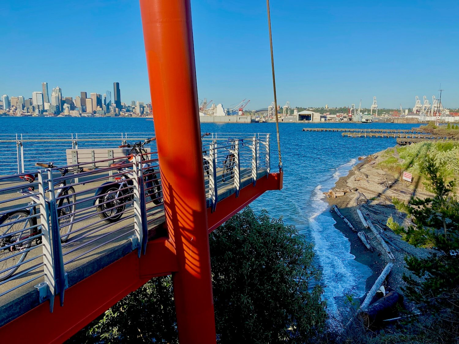 A view from high up in the observation tower at Joe Block Park in West Seattle. The structure is supported by giant orangish red tubes of metal and thick cables. The platform offers sweeping Lewis of the downtown skyline of Seattle, including the tall, black colored Columbia Center in the background. Closer to the tower there are foamy white waves rolling onto a small spit of beach with pieces of driftwood, pebbly sand and low cover bushes. The industrial area of Seattle is directly behind the beach scene.