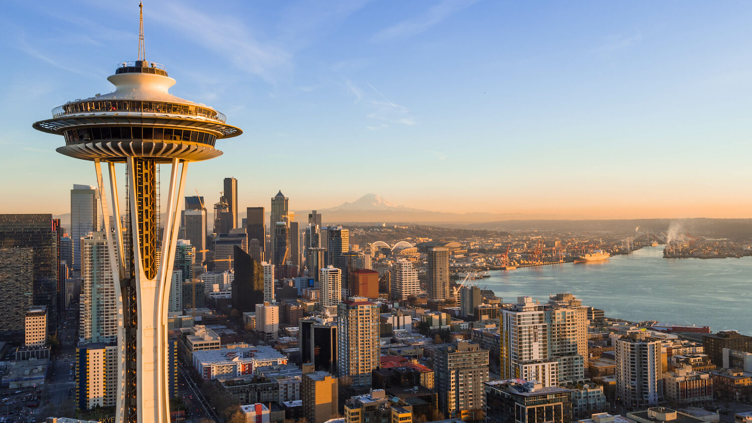 Skyline of Seattle Washington from the point of view of the Space Needle, which is in the foreground of this shot. The many buildings of the Seattle skyline crowd around Elliott Bay with the faint outline of Mt. Rainier on the peach colored horizon.