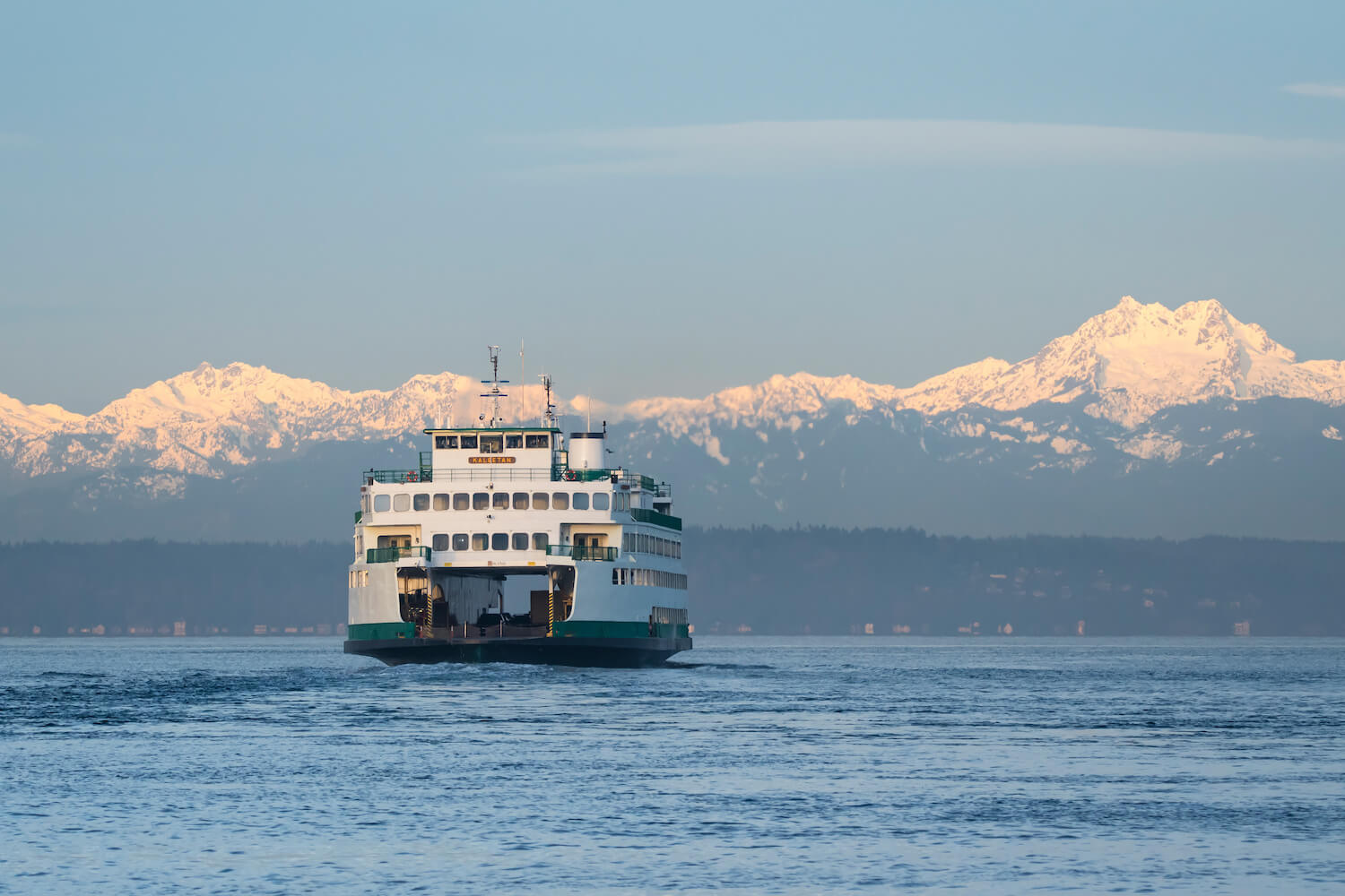 A Washington State Ferry crosses a channel of the Puget Sound, en route to the Olympic Peninsula. The snow capped mountains shine in front of a blue sky and layers of evergreen trees are seen closer to the ferry, which glides through lightly rolling water.