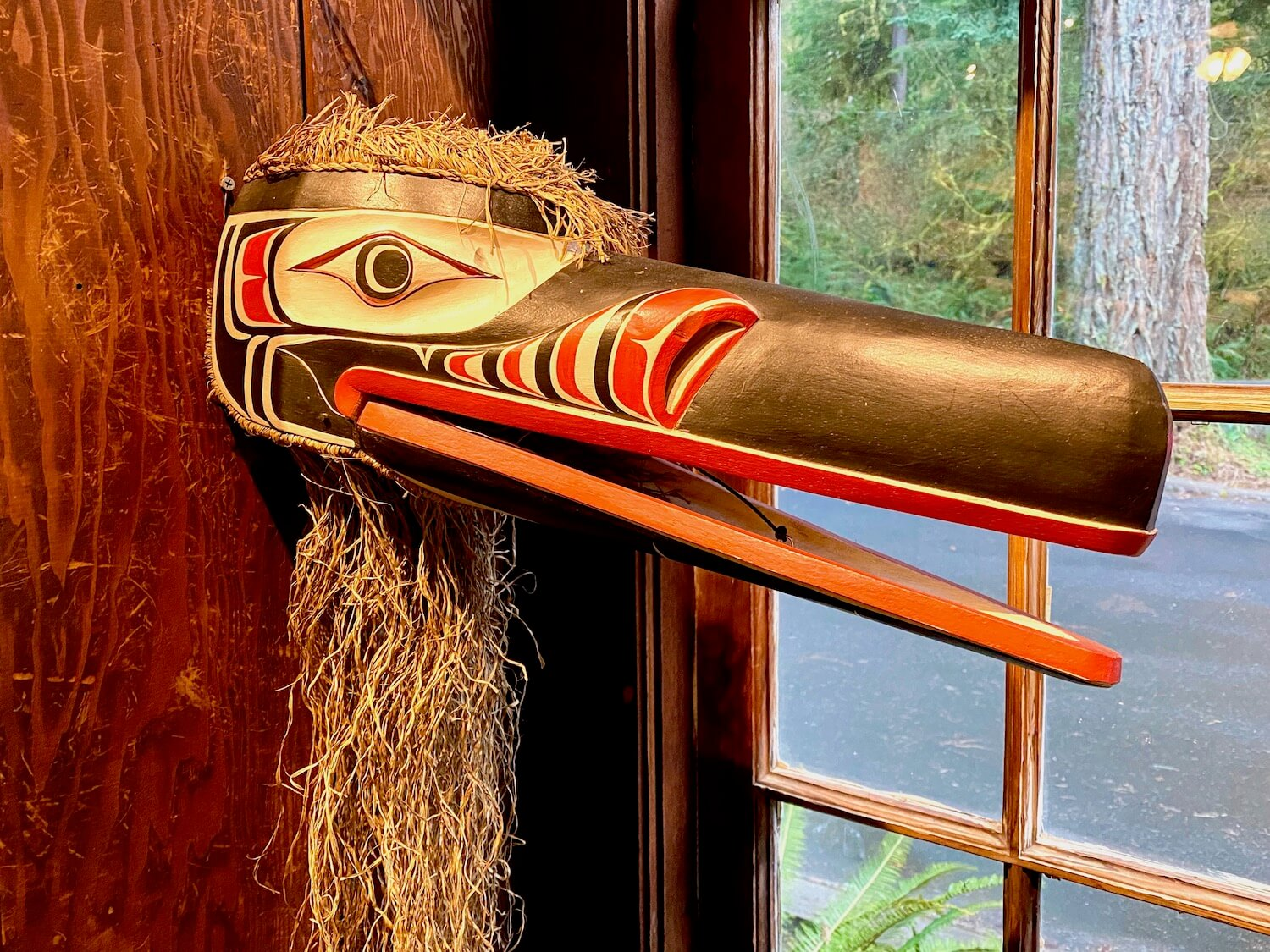 A native mask made from cedar wood and the bark of the tree depicts an ancient story about a bird. The beak is painted black with hints of bright red.