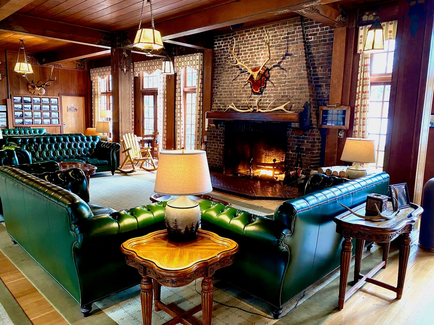 The grand lobby of the Lake Quinault Lodge has plush green leather couches welcoming guests to a roaring fire in a giant brick fireplace with Roosevelt Elk horns mounted on the mantle. Light flows through the floor to ceiling wall of windows.