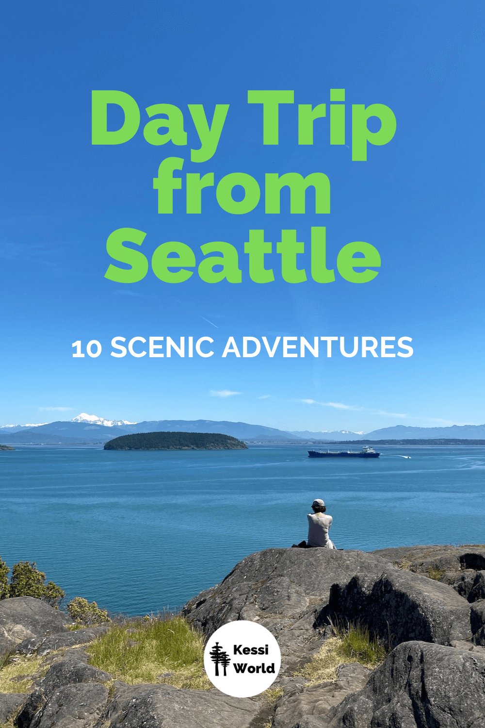 The title of this Pinterest tile reads Day Trip from Seattle and shows a scene from the viewpoint of Cap Sante Park in Anacortes, Washington. A woman sits on top of a giant boulder with other rocks around and some patches of bright green grass. She looks out towards snow capped Mount Baker and the vast water of the Puget Sound. There is a large merchant ship in the channel and a fir tree covered island. The sky is bright blue.