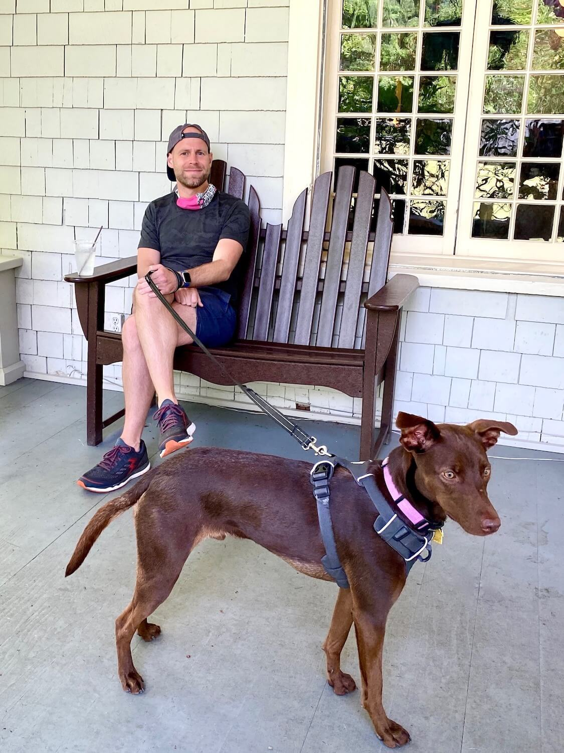 A man sits on a bench on the porch of the Lake Crescent Lodge holding a leash to a sleek brown dog with tall legs and a shiny, healthy looking coat.