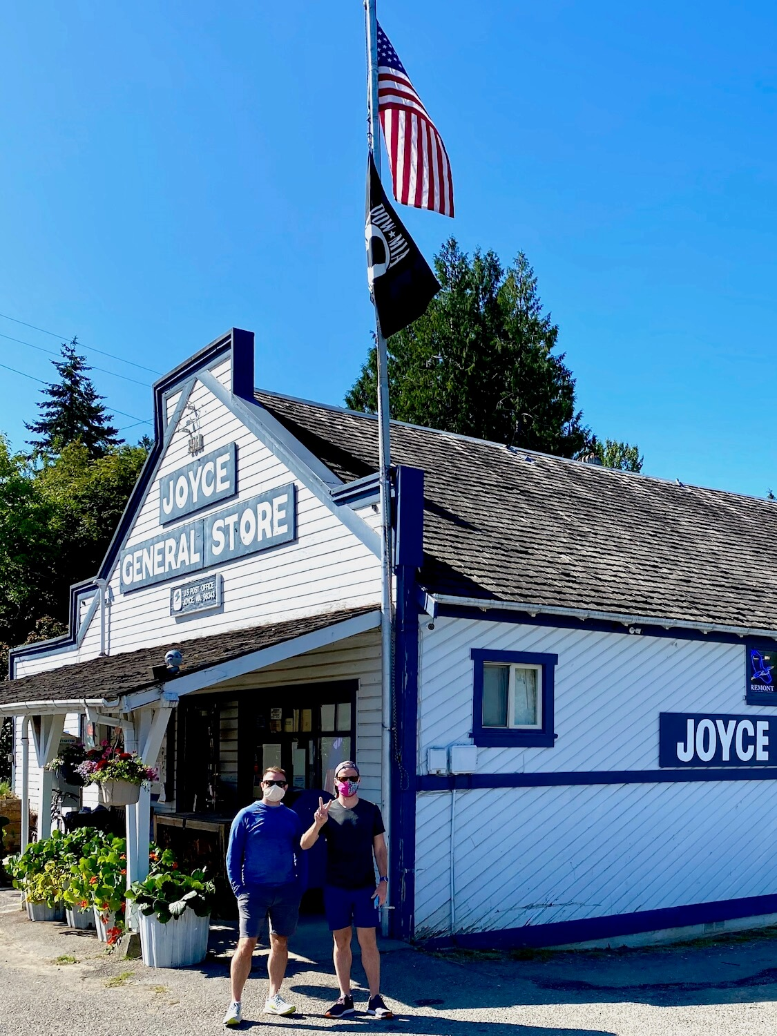 The Joyce General Store is a rustic, timeless small town meeting place. The pioneer style building is gray wood panels with bright blue trim and two men stand out from wearing face masks as a flagpole stands tall with an American flag and a black POW flag. The sky is blue and a green leaved maple tree rises up behind the age old store.