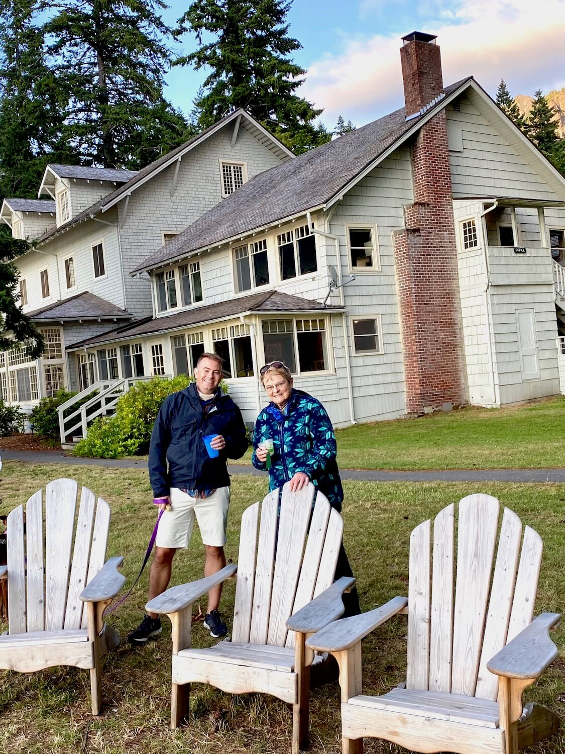 The outside of Lake Crescent Lodge in amongst nature. These two lodge visitors are enjoying a beverage next to three oversized Adirondack chairs. The sky is changing to sunset colors with a brush of pink across the otherwise blue, tree lined sky.