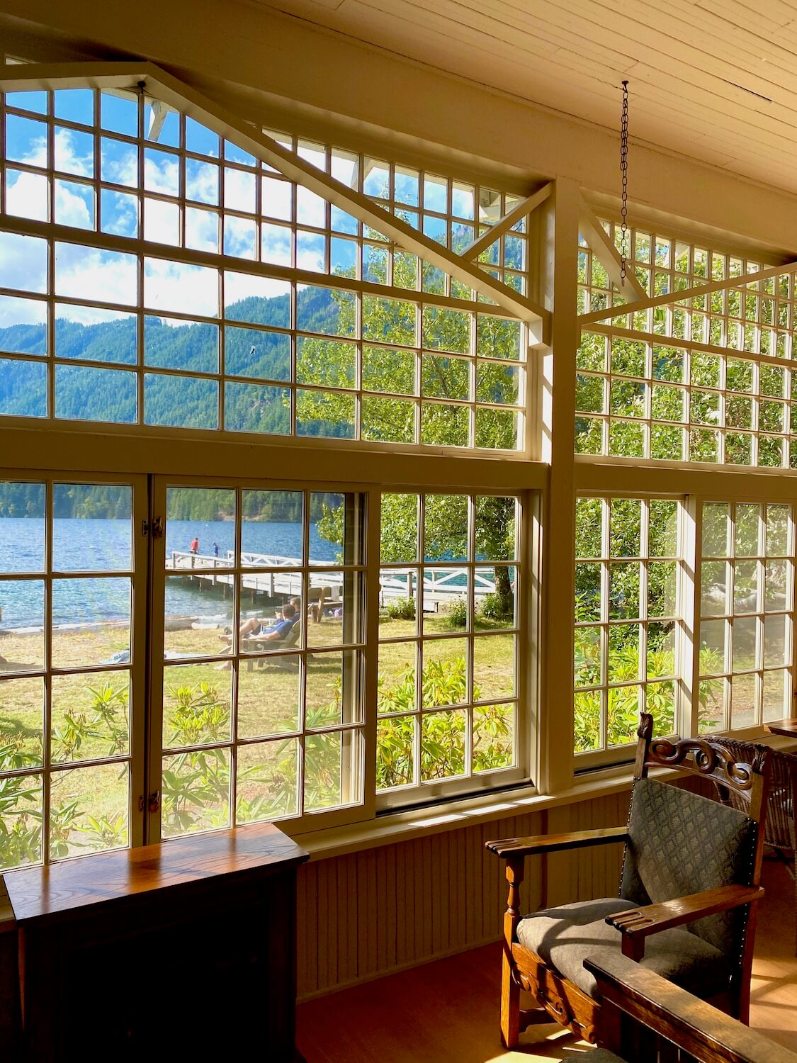 The view looking out of the Lake Crescent Lodge sunporch toward the lake and dock. They windows offer a full view and are made up of tiny panes of glass. Inside the porch is a antique brown chair.