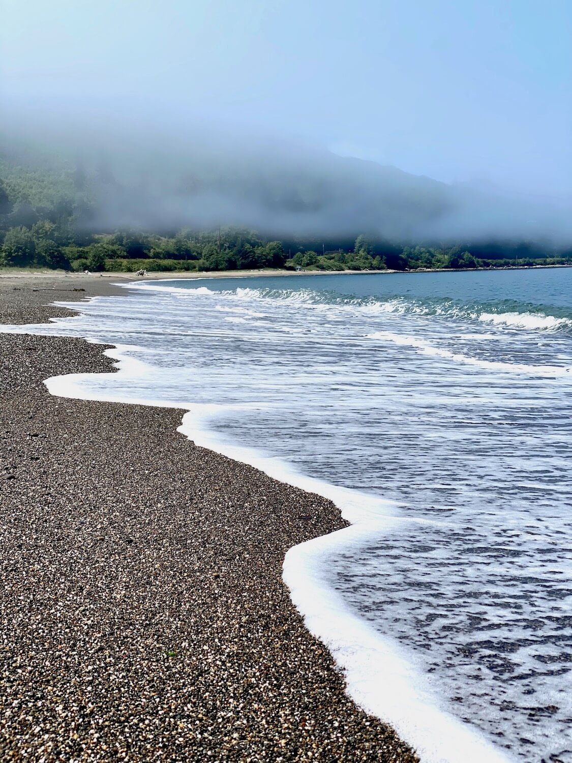 Coastal Olympic Peninsula scene with a pebble beach and soapy, white foam of the surf slathering the beach with a wavy line. In the distance the mist still hovers over the hill of trees, only revealing a faint line.