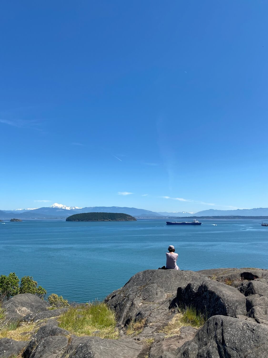 This shot shows a scene from the viewpoint of Cap Sante Park which is one of the great things to do in Anacortes, Washington. A woman sits on top of a giant boulder with other rocks around and some patches of bright green grass. She looks out towards snow capped Mount Baker and the vast water of the Puget Sound. There is a large merchant ship in the channel and a fir tree covered island. The sky is bright blue.  A day trip from Seattle to Deception Pass and Anacortes is guaranteed to provide stunning vistas of nature.