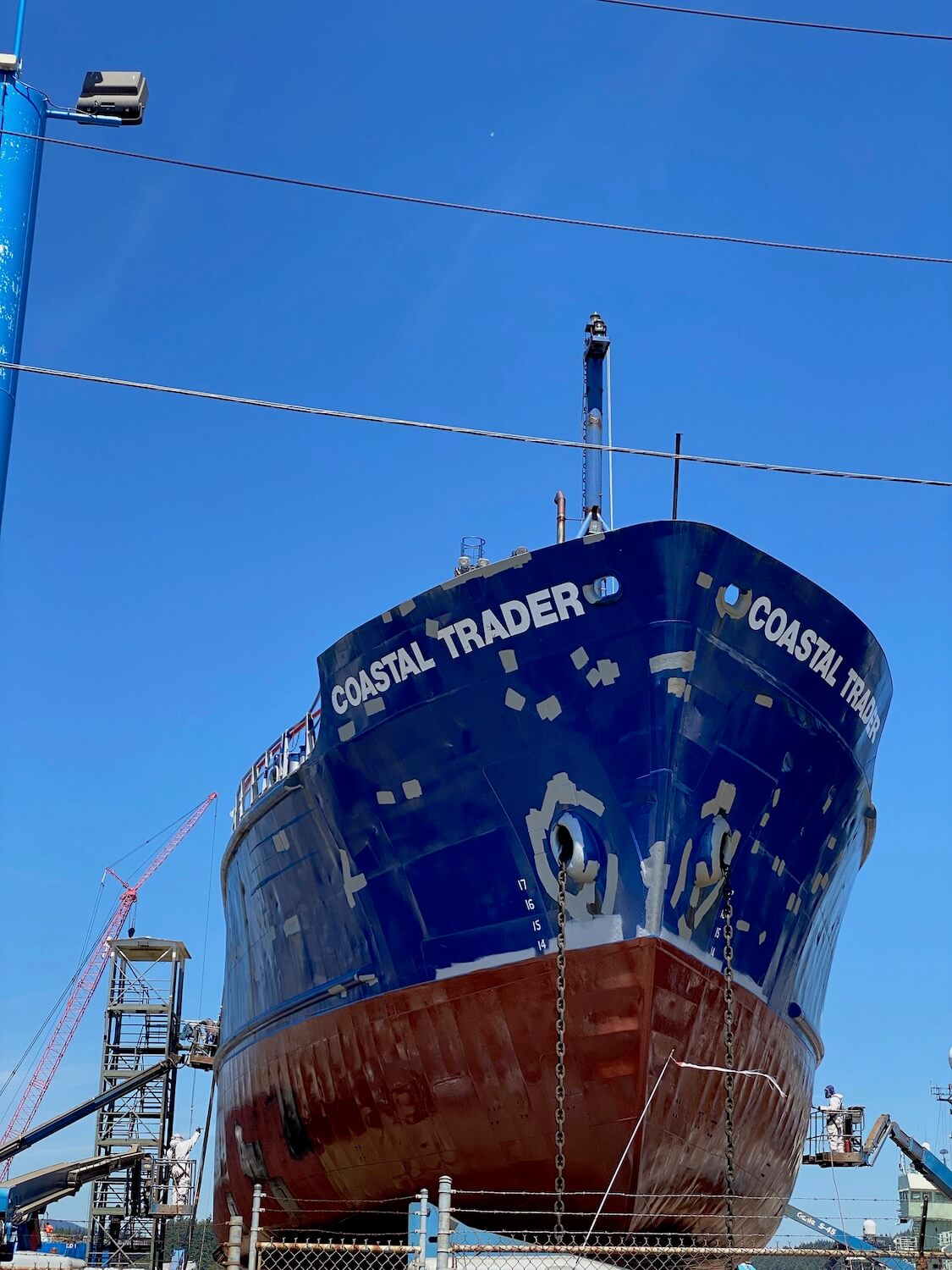 A large ship is in dry dock with large patches of gray paint dotting the otherwise dark blue hull of the vessel.  The underwater line section of the metal is painted red.  Cranes and workers are operating around the ship.