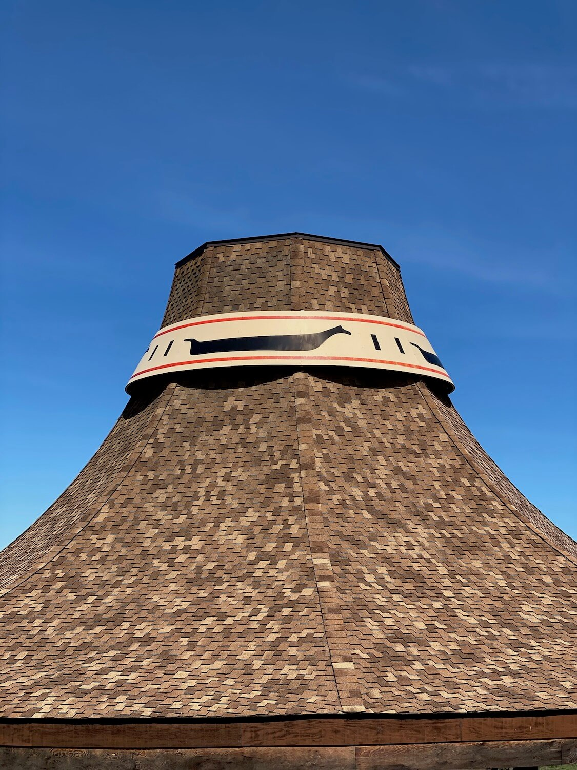A large replica of a cedar hat traditionally worn by the Swinomish people is one of three large pavilion covers erected in a park across the channel from the pioneer town of La Conner, Washington.  This is a great stop along a day trip from Seattle.