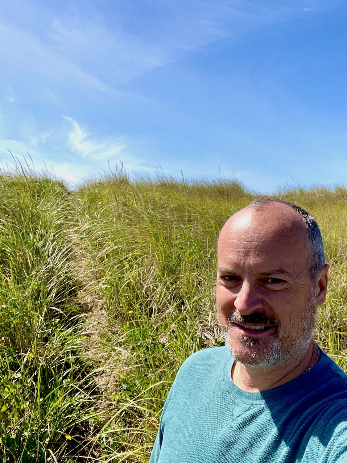 Matthew Kessi stands in a sand dune along the beach on the Washington Coast. He is smiling while the green grass pops up with sharp edges. The sky is blue in the background.
