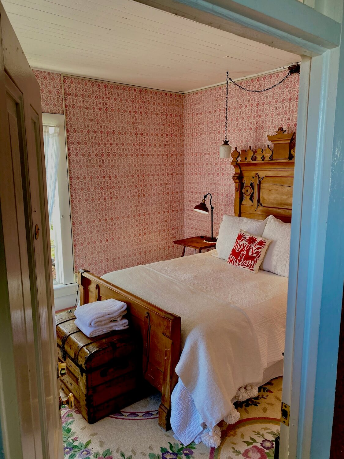 Room #1 at the Tokeland Hotel, on the Washignton Coast. This view is looking into the room from the hallway. The room has wallpaper with bright red geometric circles and a white wood slat roof. The bedspread is white and the ornate headboard made from a walnut looking wood.