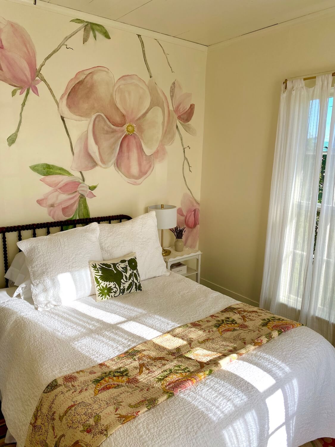This photo of a room at the Tokeland Hotel on the Washington Coast shows a light filled room with a queen sized bed with cream colored walls and a magnolia tree branch and pink flower etched on the wall in water colors.