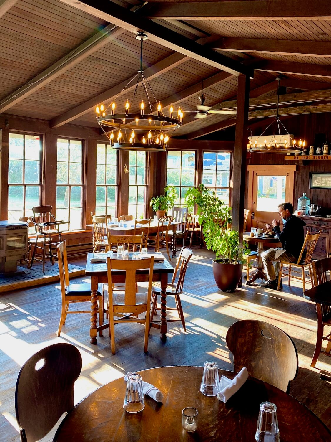 The rustic wood paneled vaulted ceiling of the restaurant at the Tokeland Hotel allows light to flow in through the eight panel pioneer style windows. Another restaurant patron is sitting at a table in the background eating breakfast.