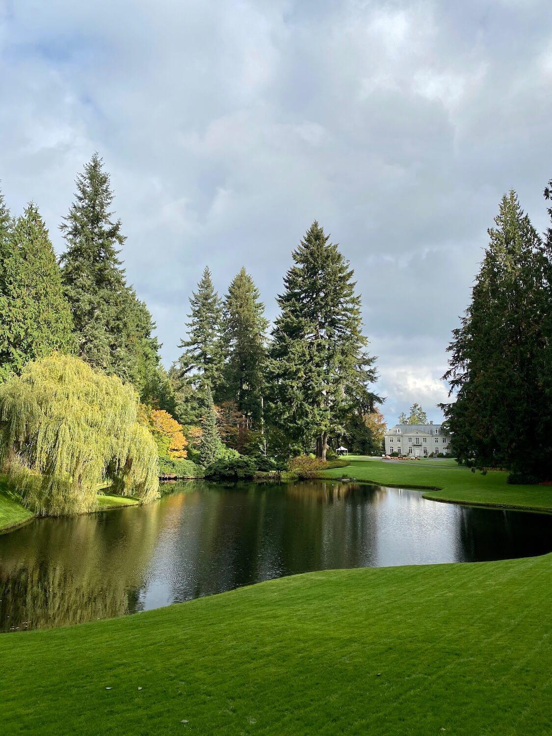 The Residence at Bloedel Reserve on Bainbridge Island sits regally above a large grassy lawn that surrounds a peaceful lake.