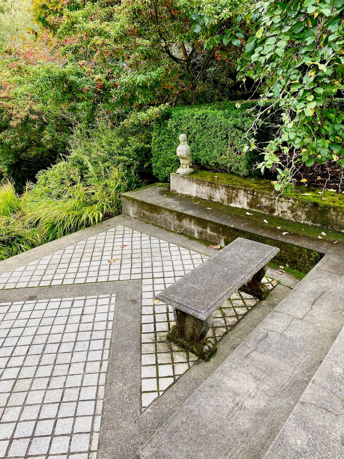 A concrete bench with ornate feet sits on a grid of square bricks and is surrounded by green shrubbery.