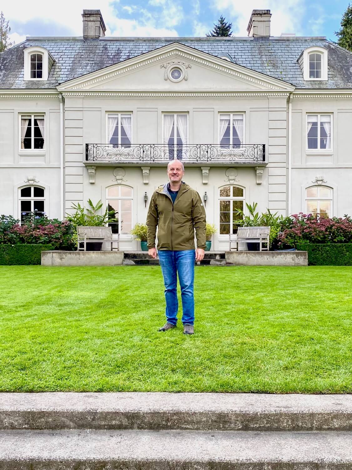 Matthew Kessi stands in front of the grand lawn of the Residence at Bloedel Reserve on Bainbridge Island. The three Storie elegant concrete house has windows with curtains and a slate roof. Two smoke stacks rise up to the blue sky above.