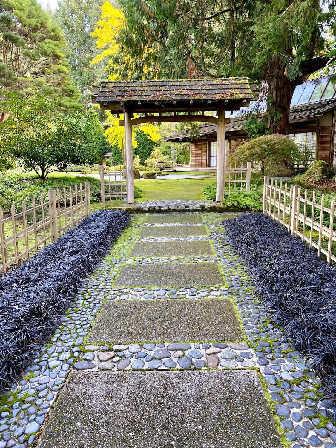 An ornate entrance to the Japanese Garden and Guest House at Bloedel Reserve. The wooden archway is followed by intricate bamboo lattice fence that is surrounded by blackish purple grasses. The path is a mixture of rocks and concrete pavement.