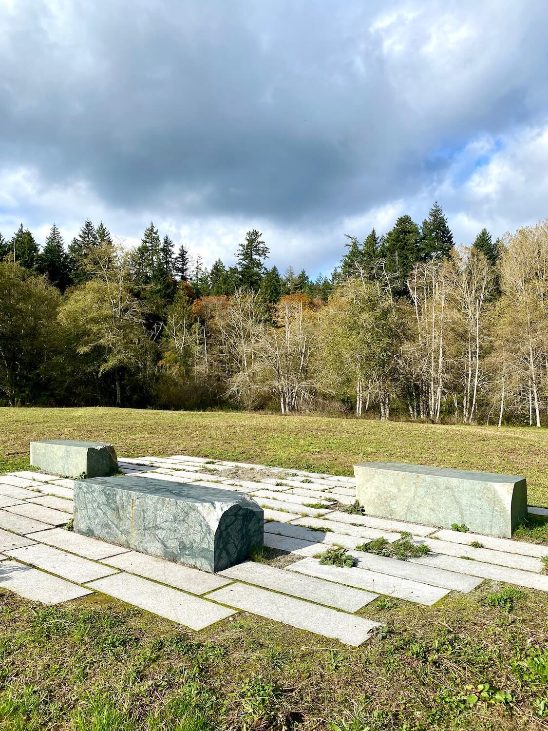 Three large granite blocks are assembled in the middle of a mowed grass field on a hillside in Bloedel Reserve. At the end of the field there are birch trees with changing leaves for fall season and a few evergreen trees behind them. The sky has an angry swirl of dark gray in amongst lighter colors of blue and white.