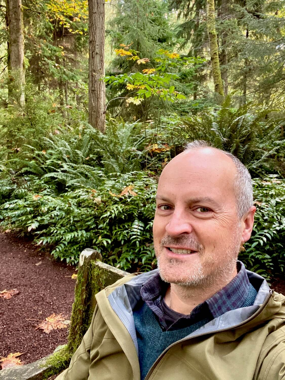 Matthew Kessi sits at a moss covered bench in amongst a woods setting, with green sword fern and low Pacific Northwest forest brush in the background. There is a bark dust trail behind him.