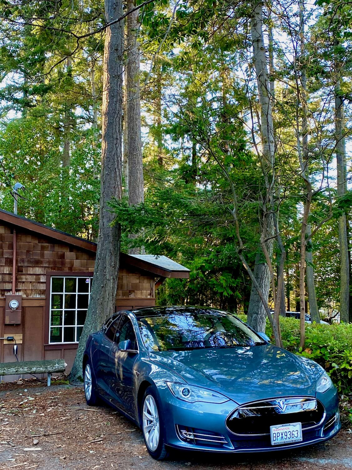 An electric vehicle charges along side a brown building with cedar shake siding. The electric meter is seen next to the box connecting to the vehicle which is situated under coastal fir trees.