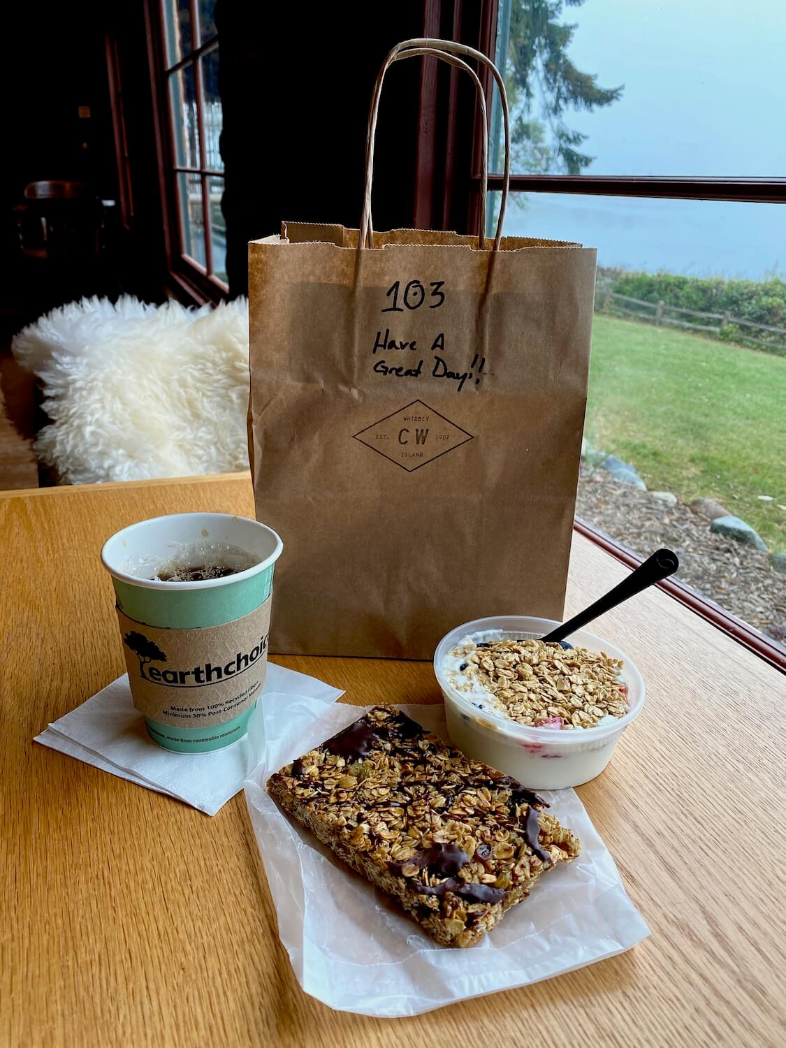 """A breakfast bag at Captain Whidbey is made from recycled paper and says, """"Have a great day."""" On the wood table is a cup of coffee in a to-go cup along with a granola chocolate bar as well as yogurt with a spoon in it. The chair on the other side of the table is draped with a fuzzy wool throw while the green grass and blue waters of Penn Cove are visible outside the window."""