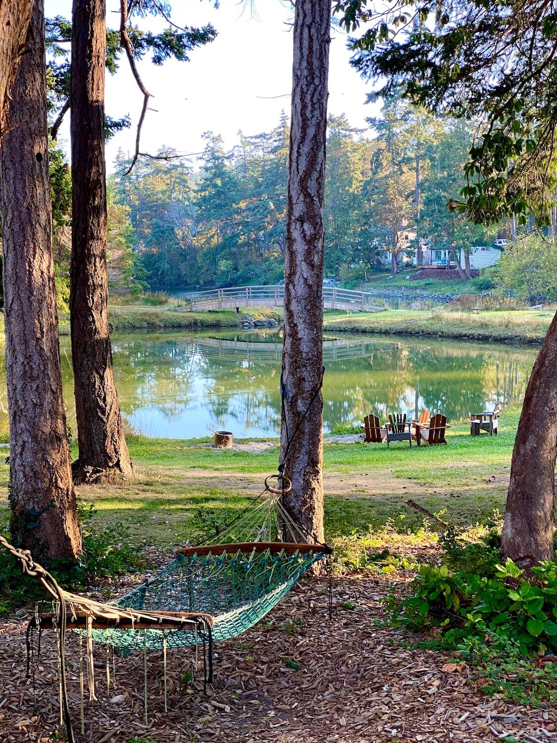 A peaceful forest setting shows a green woven hammock hanging between two pine trees that looks out toward a green lagoon with adairondack chairs situated in clusters facing the water. There is green grass and a wooden bridge that arches over the waterway leading to nearby Penn Cove.