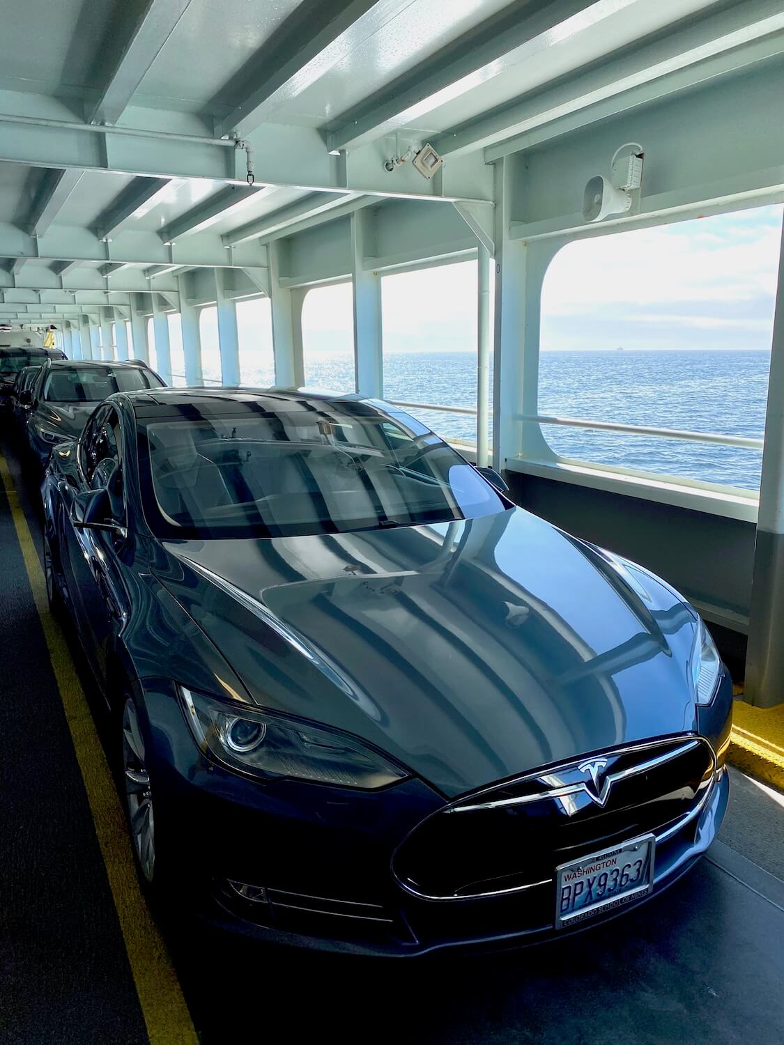 The Tesla beginning a road trip around the Puget Sound, on board a Washington State Ferry.  The car is in line with many others amongst metal beam structures against the flowing water beyond.