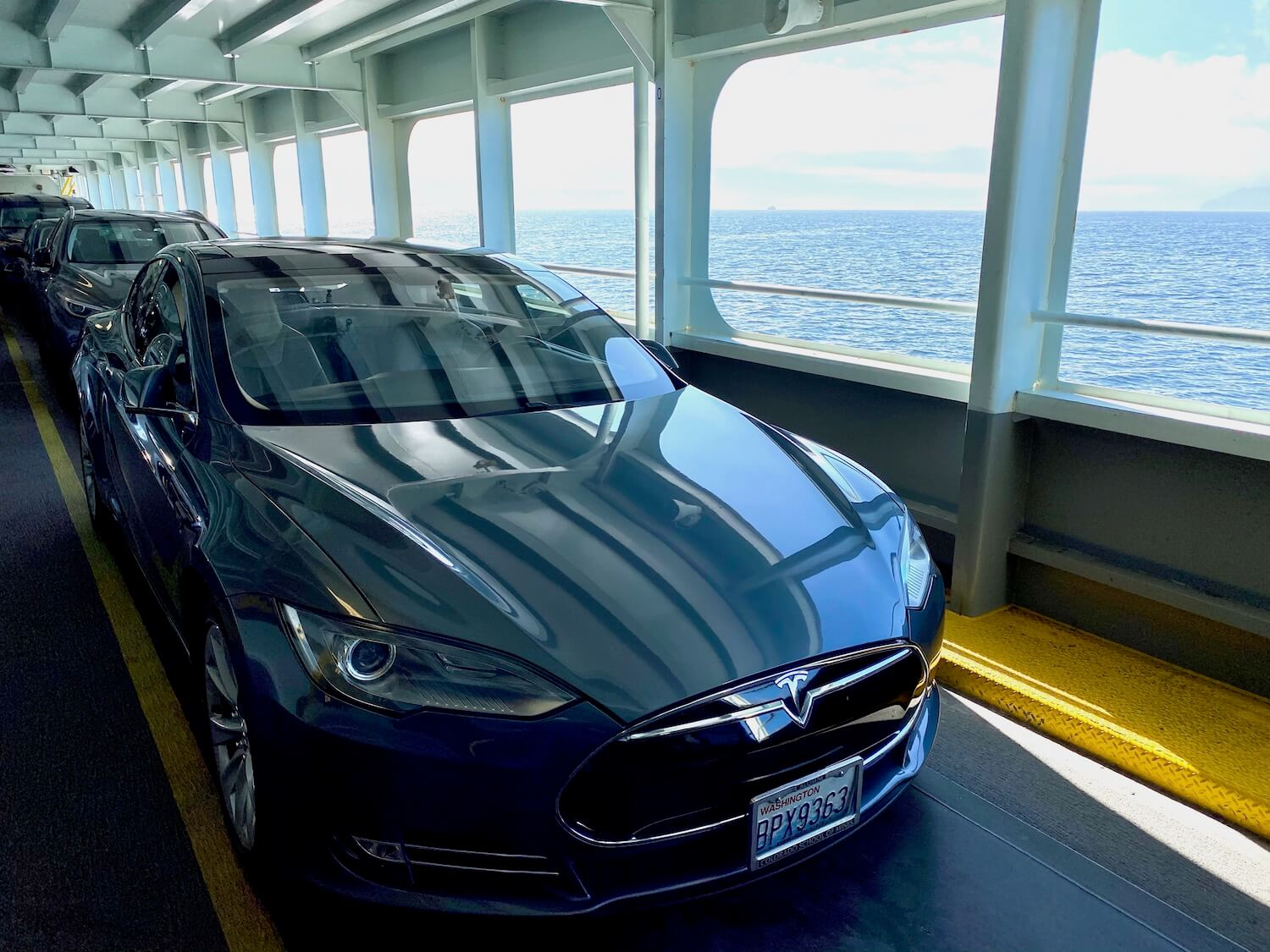 A Tesla Model S sedan sits on the deck of a Washington State Ferry with open Puget Sound waters in the distance against a cloudy sky. The vehicle is a metallic gray blue and shows the prominent Tesla hood ornament on the front. There are other cars behind the Tesla and the metal structure of the ferry are painted white on the ceiling above.
