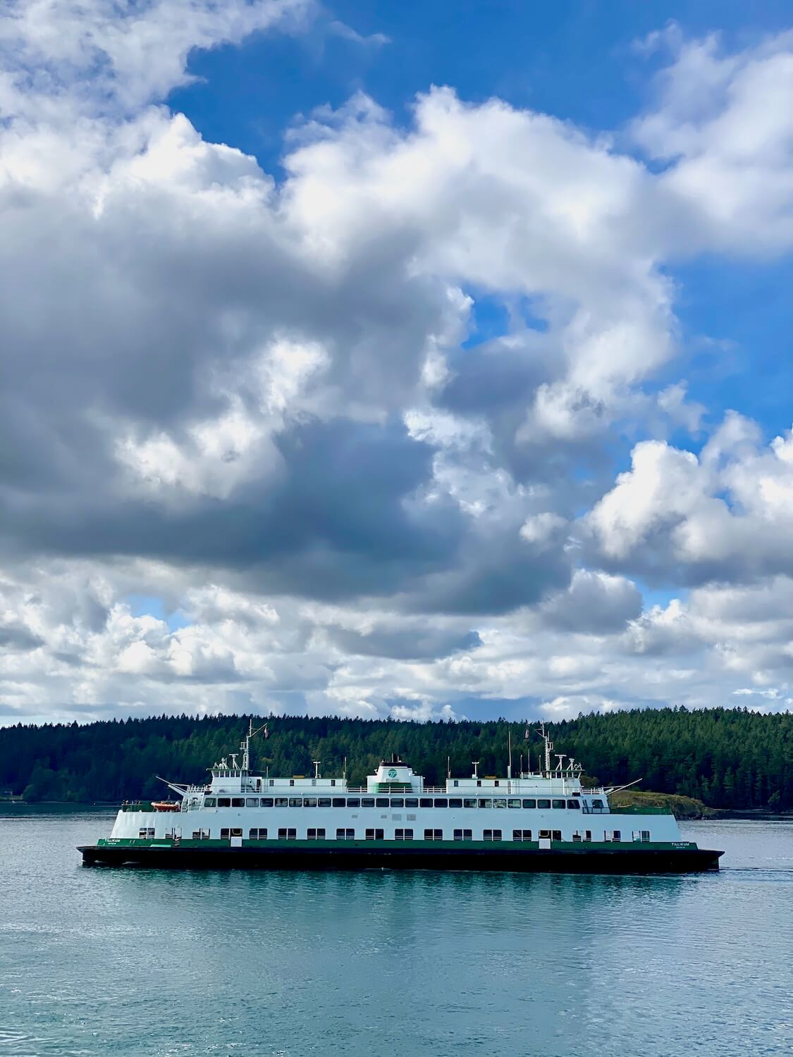 A Washington State Ferry crossing through the water of the Puget Sound. The two level ferry is painted white with green trim and passes in front of an island covered with green fir trees. Up above the clouds form gray and white patches amongst a bright blue sky.
