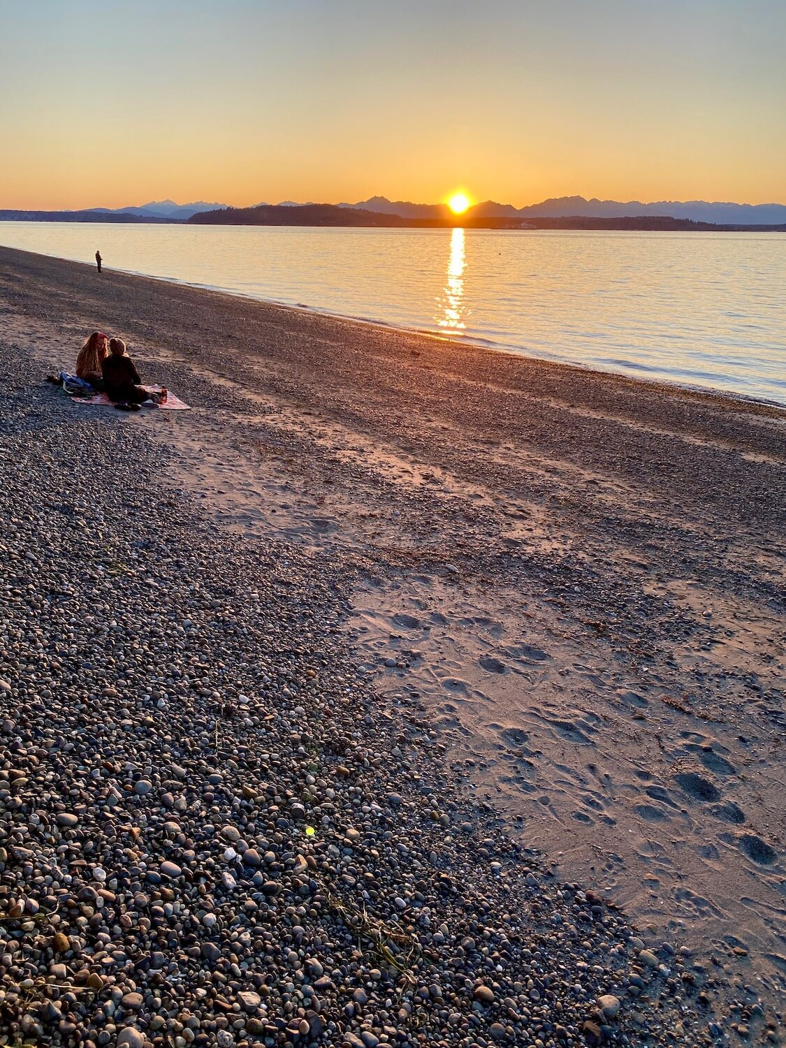 An orange glowing sun sets behind the Olympic Mountains as the rays shine on the vast Puget Sound waters. A couple enjoys the sunset on a blanket on the beach. This is a great winter outdoor thing to do in Seattle.