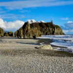 A beautiful beach scene combines bright blue skies with some puffy white clouds and rock stacks indicative of the Washington Coast. The surf is crashing waves onto the rocky beach revealed by low tide.