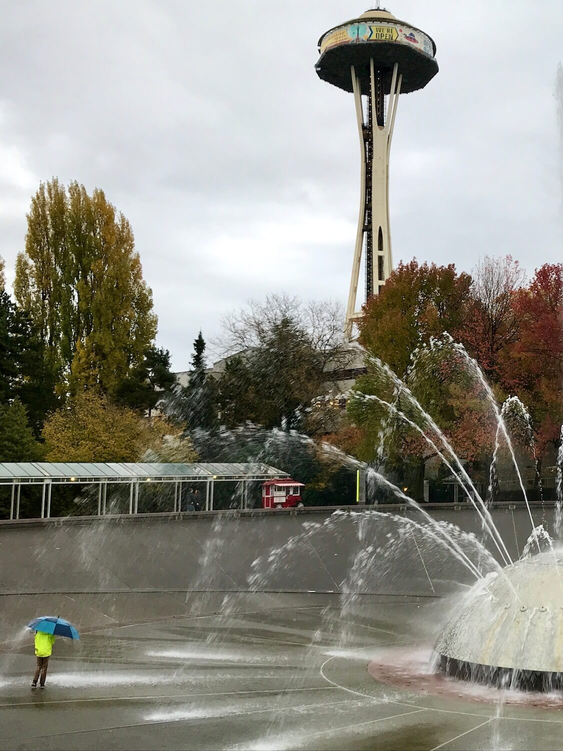 A boy wearing a yellow rain jacket approaches the large fountain with a blue umbrella. The metal piece of art shoots out powerful streams of water in all kinds of directions. In the background the Seattle Space Needle rises up above the park at Seattle Center.