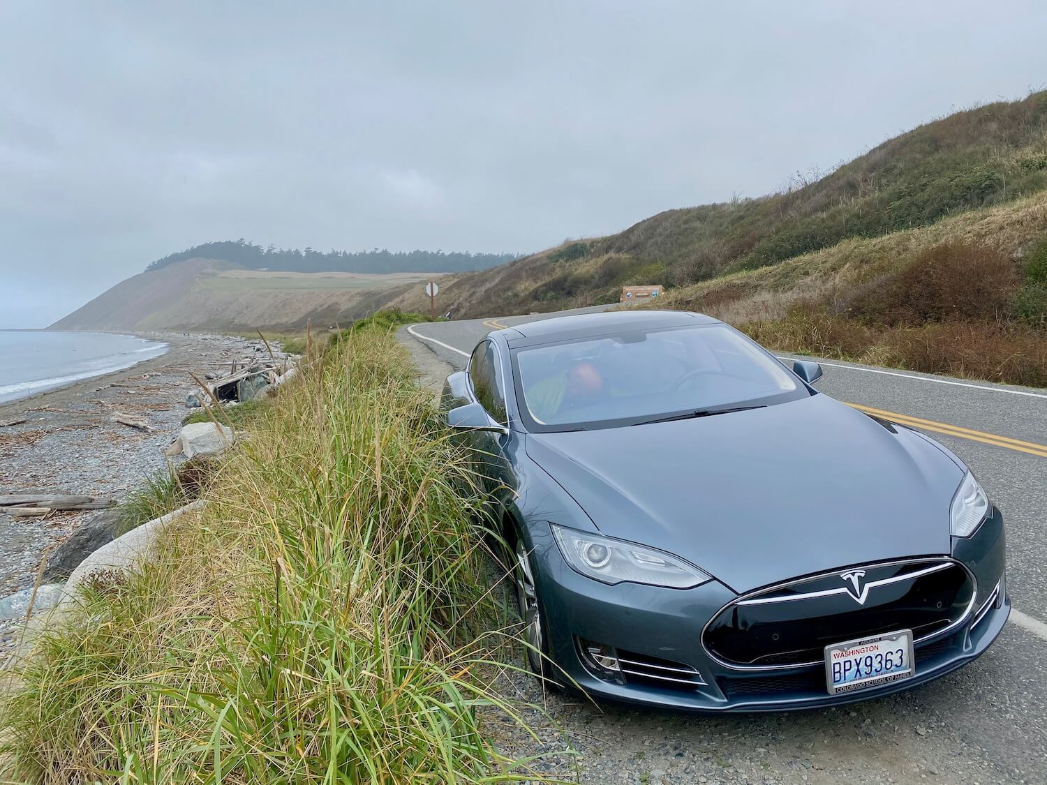a gray Tesla sits on the side of a road just on the edge of a bank leading down to a beach on Whidbey Island in the middle of the Puget Sound