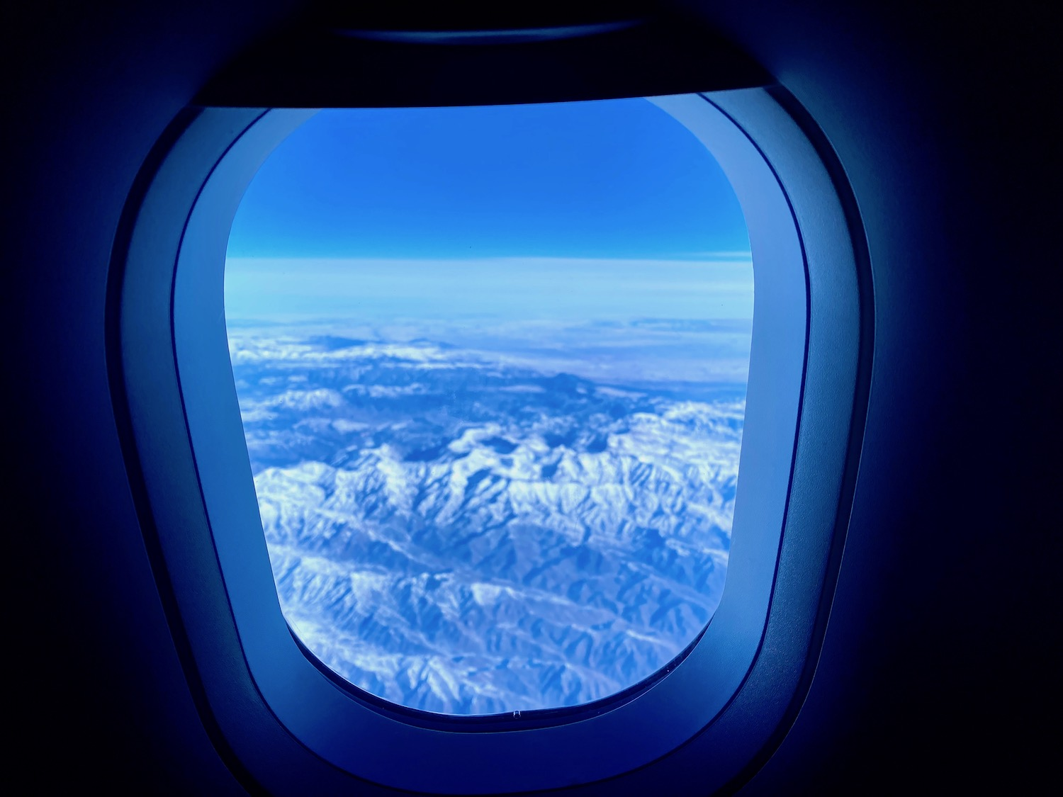 A view through an airplane window looking out at mountains covered in snow.
