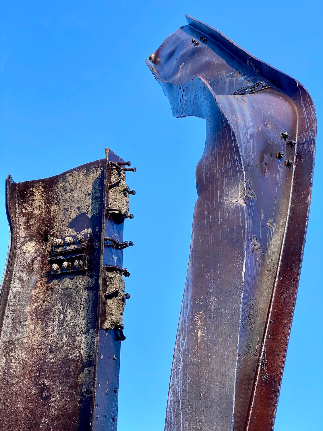 Two steel girders salvaged from Ground Zero following the attacks on the World Trade Center on 9/11.  They are purplish in color and show parts of concrete still attached to the steel and bolts loosely hanging onto the steel.  The sky in the background is a strong blue color.
