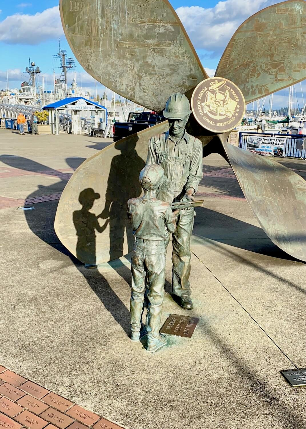 A bronze statue of a father passing on a shipbuilding tool to his young son. They are standing in front of a giant propulsion screw of a ship.