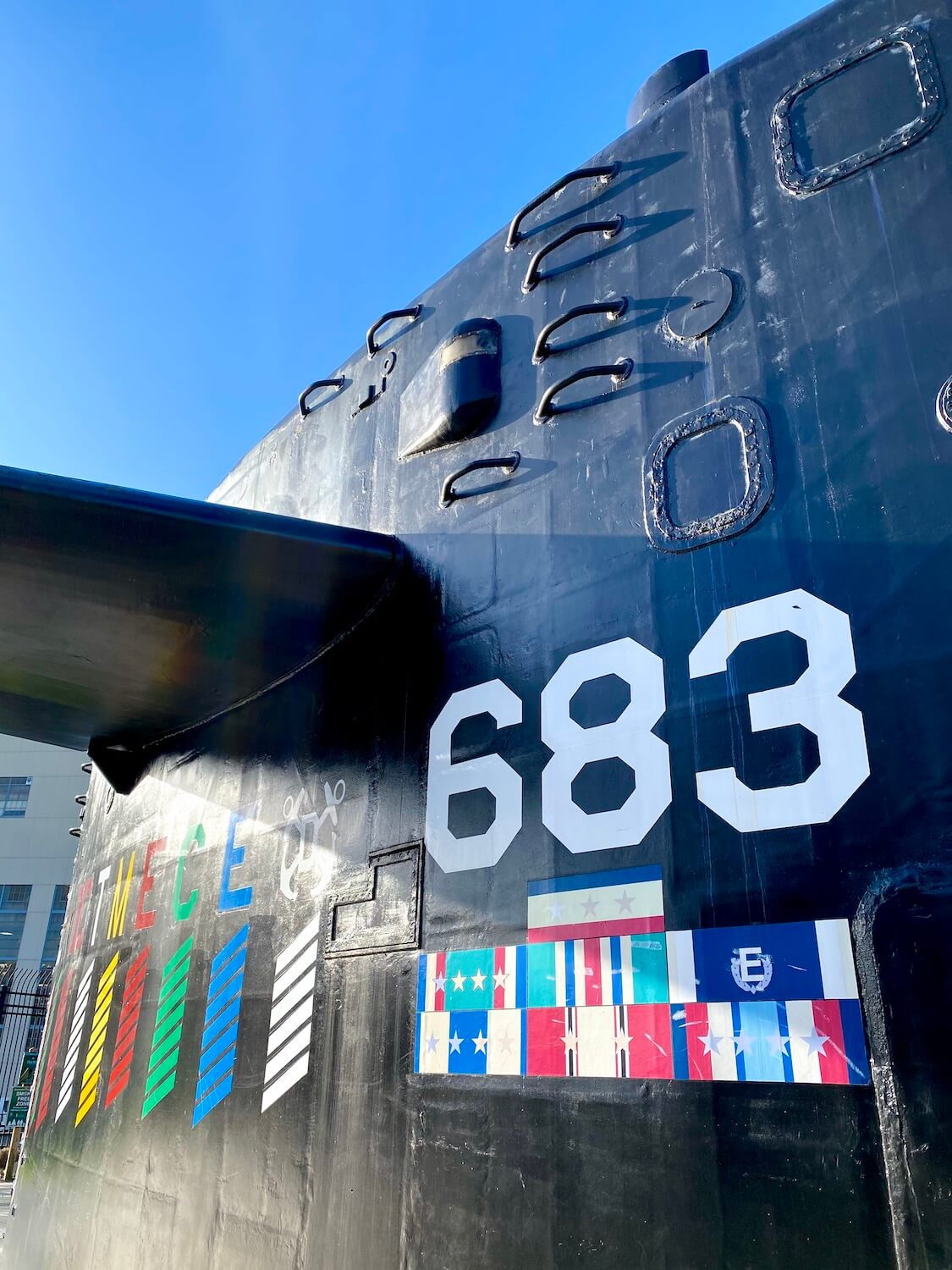 An up close photo of the sail of the USS Parche is great thing to visit in Bremerton on a day trip from Seattle.  The sail is painted black with white numbers and the sky is blue above.