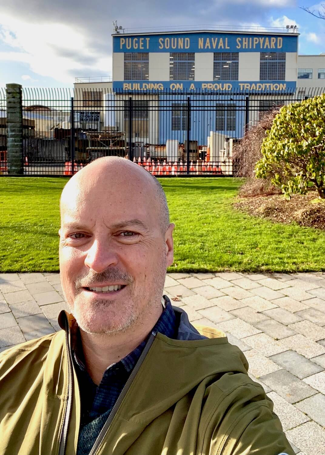 A selfie of Matthew Kessi in front of the Puget Sound Naval Shipyard in Bremerton, Washginton.  The grass is green in the background in front of a black iron grate fence leading to the industrial area.